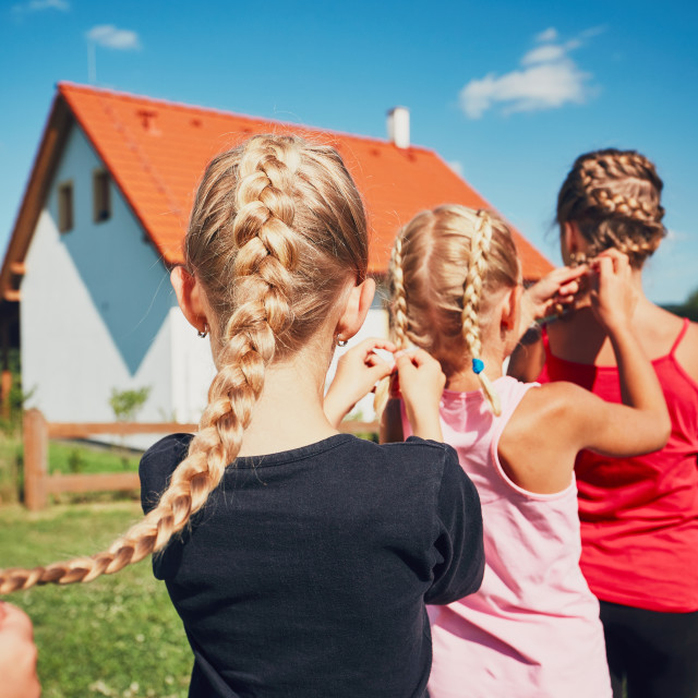 """Girls each to other making hair braids of the little girl on the garden in the countryside."" stock image"