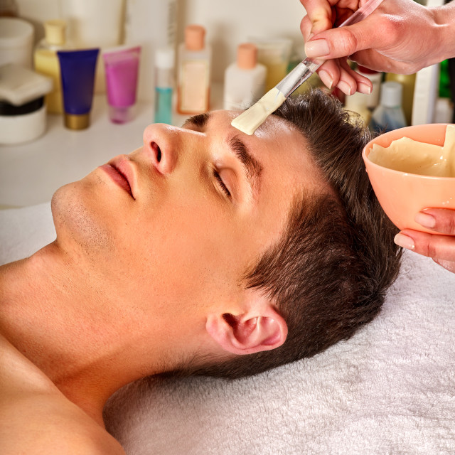 """""""Mud facial mask of man in spa salon. Face massage ."""" stock image"""