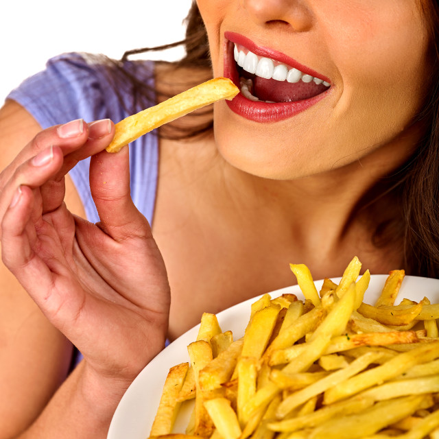 """Woman eating french fries on table."" stock image"