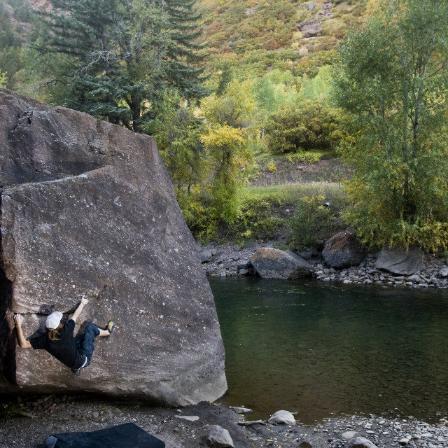 """""""A male rock climber working on a bouldering problem in Colorado."""" stock image"""