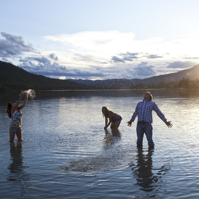 """Three young adults smile while splashing water at sunset in Idaho."" stock image"