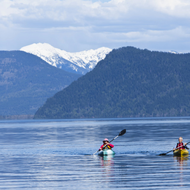 """An happy adventurous retired couple kayaking on a huge calm lake in Idaho."" stock image"