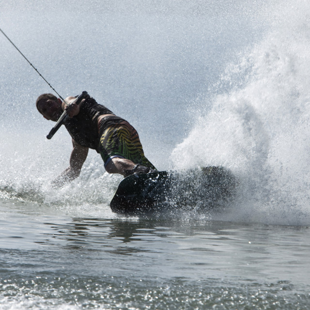 """""""A athletic man wakeboarding slashes a wave in Idaho."""" stock image"""