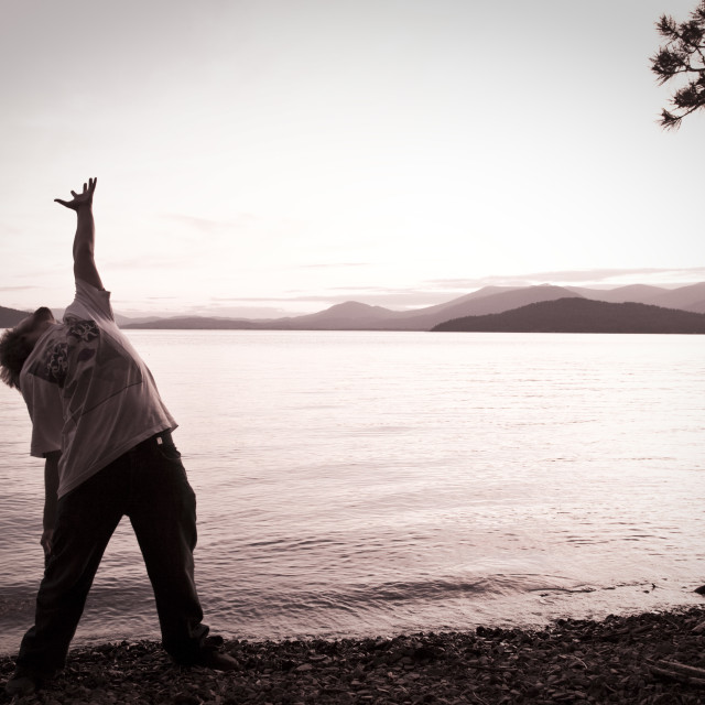 """A man arches his back with his hand stretched to the sky at sunset next to a..."" stock image"