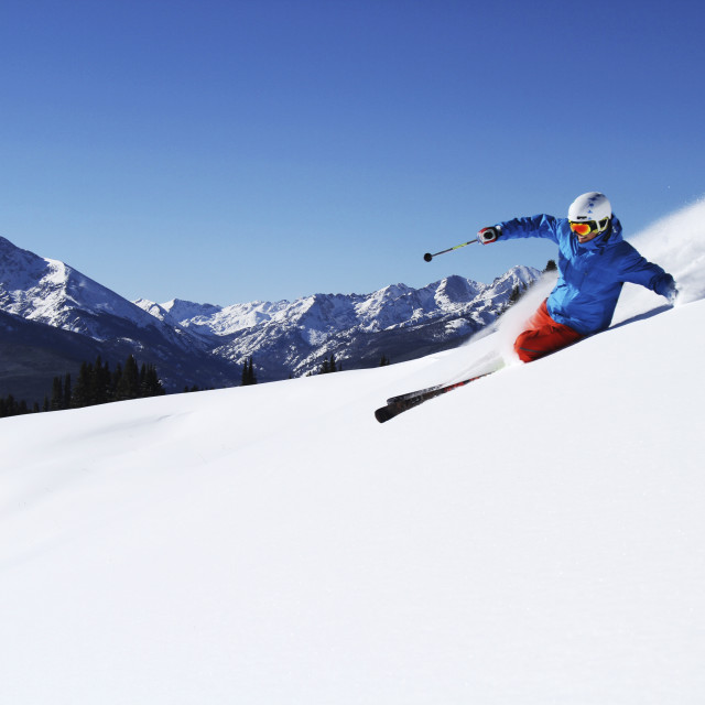 """""""A athletic skier rips fresh powder turns on a sunny day in Colorado."""" stock image"""