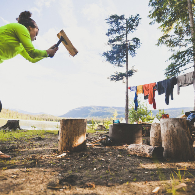 """A young woman chops firewood with a small axe while camping at Unna Lake in..."" stock image"