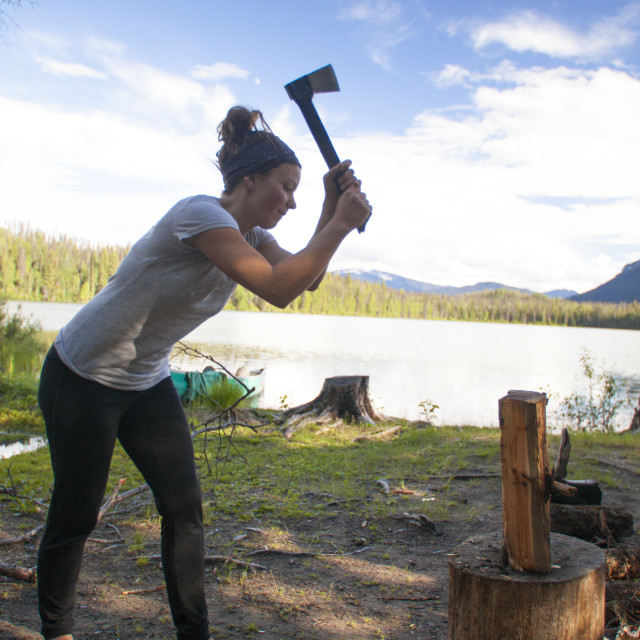 """A woman chops firewood with a small axe while camping at Unna Lake in Bowron..."" stock image"
