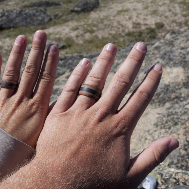 """""""A young couple wear matching wooden rings during a backpacking trip."""" stock image"""