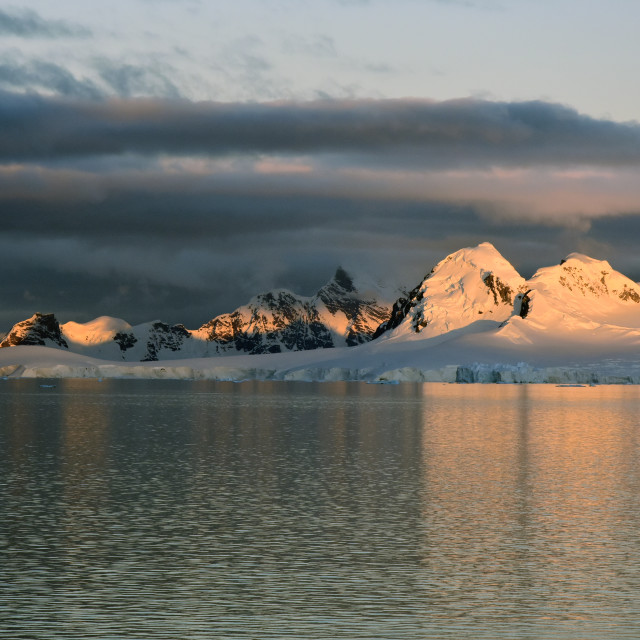 """Views of mountains at dusk, illuminated by sun in Antarctica"" stock image"