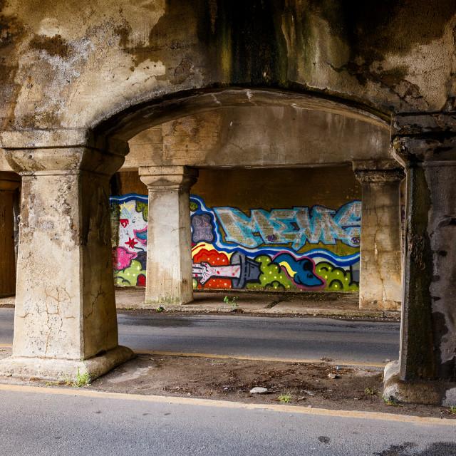 """Graffiti on a wall underneath a bridge"" stock image"