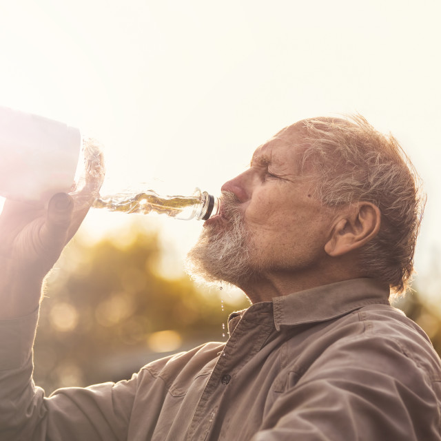 """Senior drinks water outdoor"" stock image"