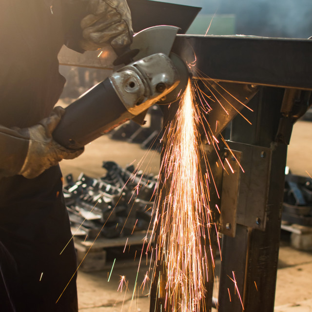 """""""Man grinding metal with angle grinder"""" stock image"""