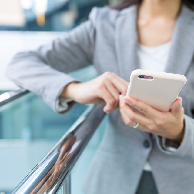 """Businesswoman sending sms on mobile phone"" stock image"