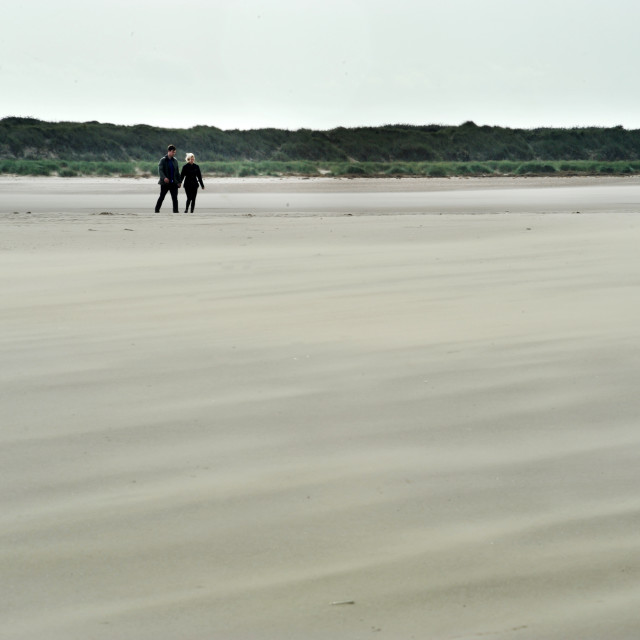 """Walking on the windswept beach - near Burnham Overy Staithe, Norfolk"" stock image"