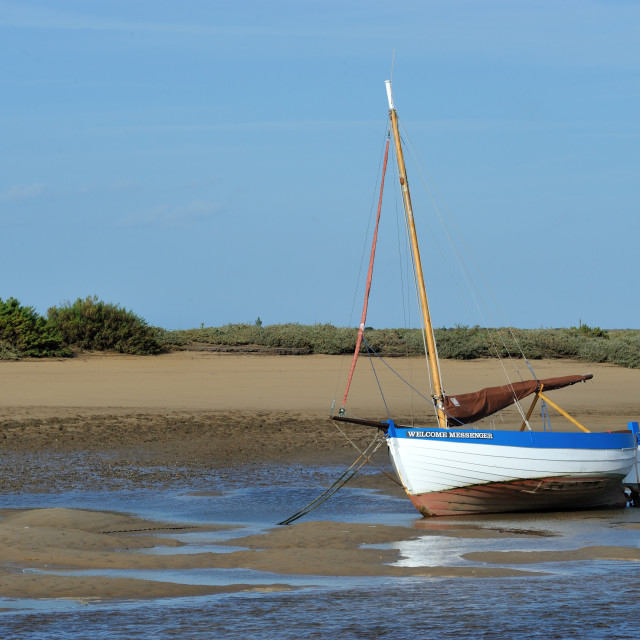 """Boat lies at low tide - Burnham Overy Staithe, Norfolk"" stock image"