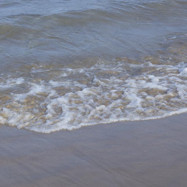 """Sand on beach by ocean"" stock image"