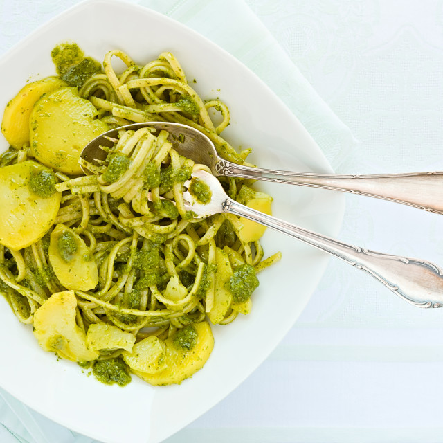 """""""Closeup of linguine pasta with pesto genovese and potatoes over a table"""" stock image"""