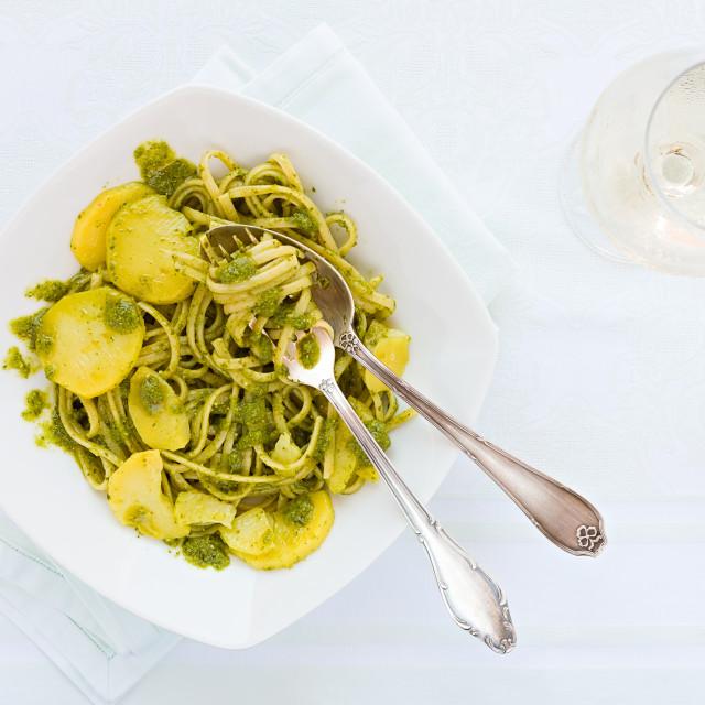 """Linguine pasta with pesto genovese, potatoes and white wine glass"" stock image"