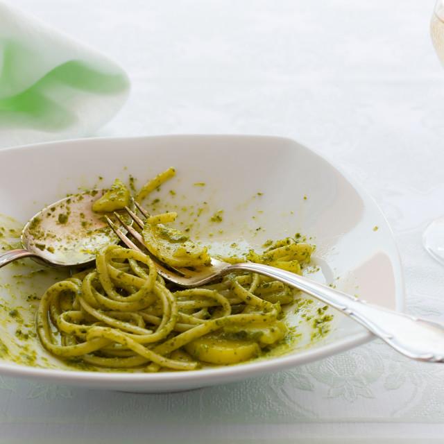 """Closeup of eaten linguine pasta with pesto genovese and potatoes"" stock image"