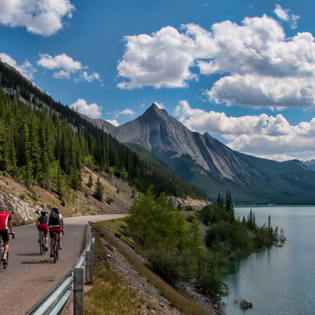 """Three Cyclists On Road With Mountains"" stock image"