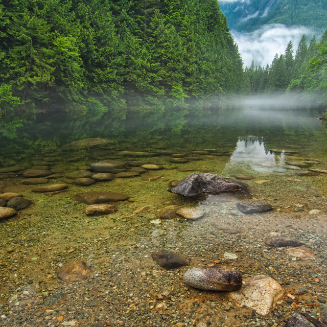 """Clear Lake With Rocks and Mist in Distance"" stock image"