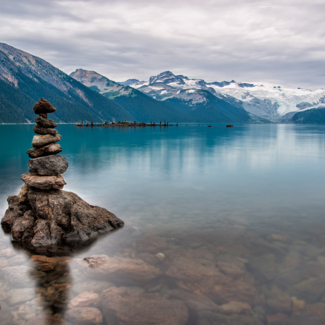 """Pile of Rocks on Turquise Lake with Distant Mountains"" stock image"