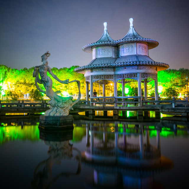 """Statue and Chinese Gazebo on lake at night"" stock image"