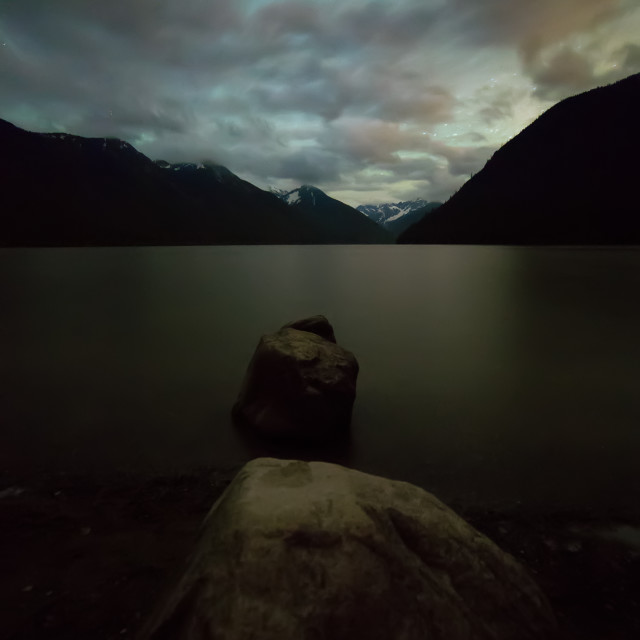 """Silhouetted Rocks on Lake at Night"" stock image"