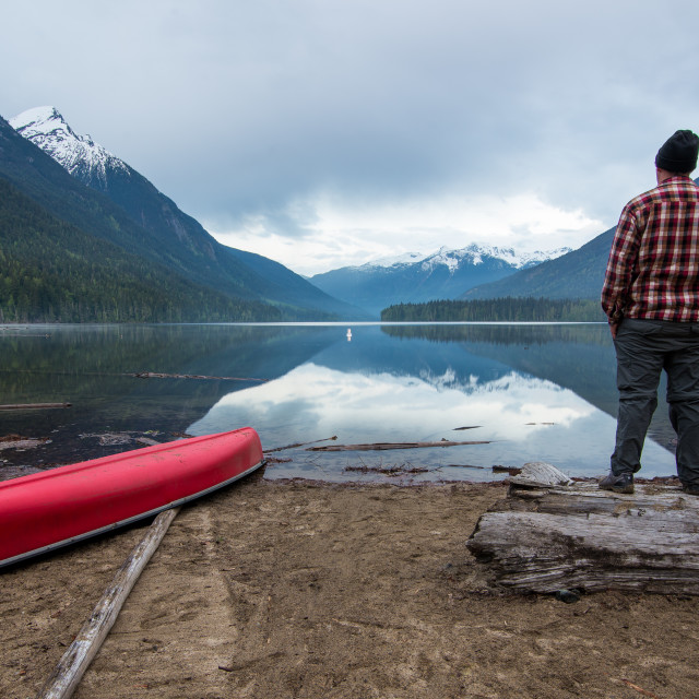 """Man Standing Enjoying View of A Lake"" stock image"