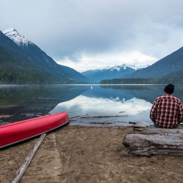 """Man Sitting Looking at Lake with Canoe"" stock image"