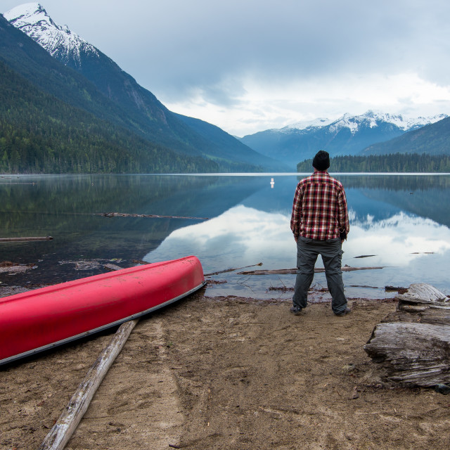 """Man Standing on Short Looking at a Lake"" stock image"