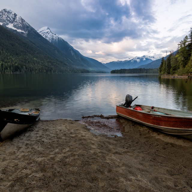 """""""Distant mountains with two boats on sandy shore"""" stock image"""