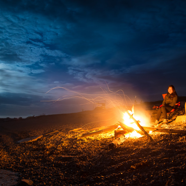 """Couple With Campfire on Rocky Beach at Night"" stock image"