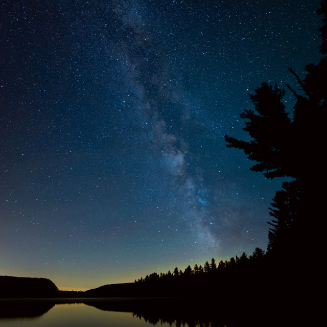 """Milky way over lake with trees"" stock image"