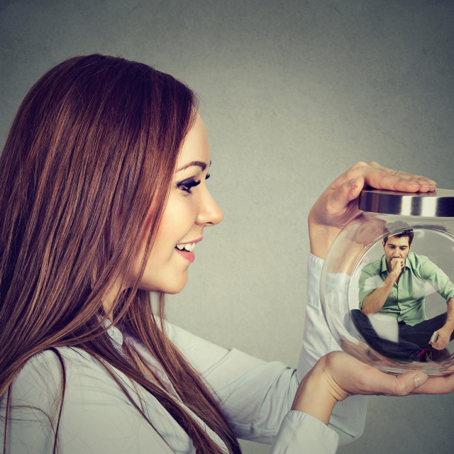 """Woman holding a glass jar with imprisoned man in it"" stock image"