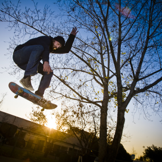 """Skater jumping at sunset"" stock image"
