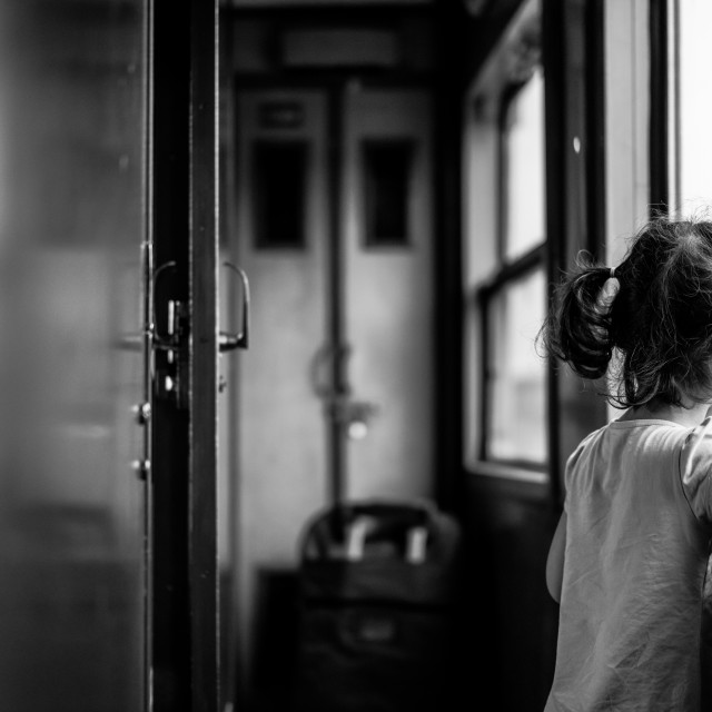"""A little girl looking the rain inside the old train in Vietnam"" stock image"