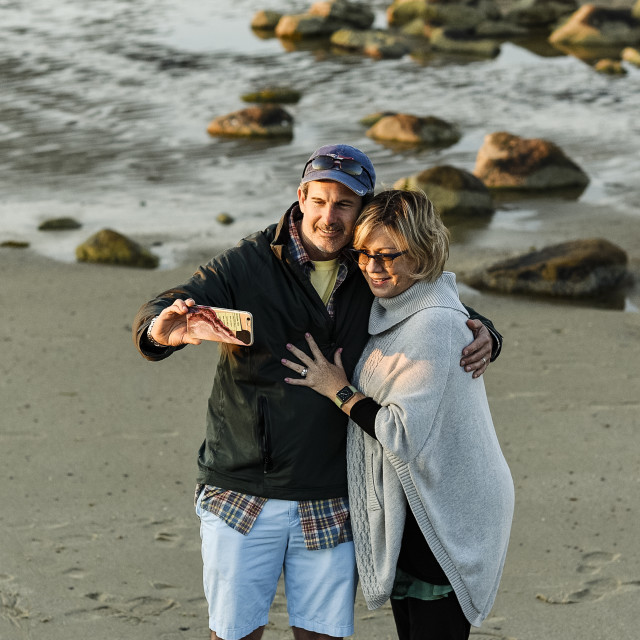 """""""Couple posing for a selfie at the beach."""" stock image"""
