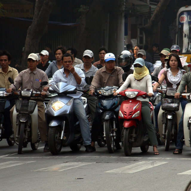 """""""Moped riders wait for the lights to change in the centre of Hanoi city,..."""" stock image"""