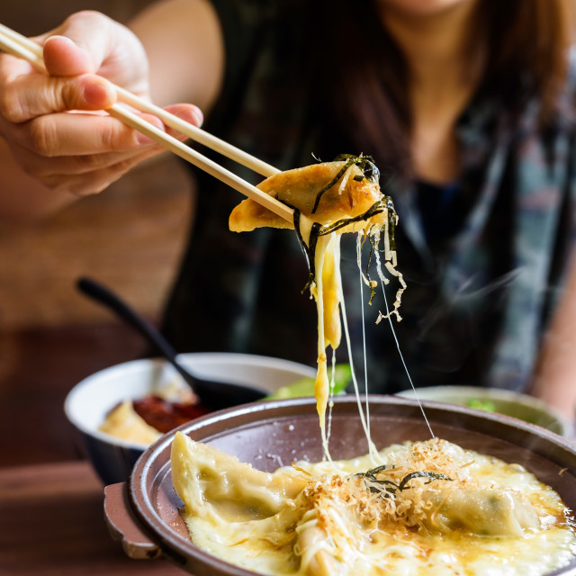"""Gyoza with melt cheese took by chopsticks"" stock image"