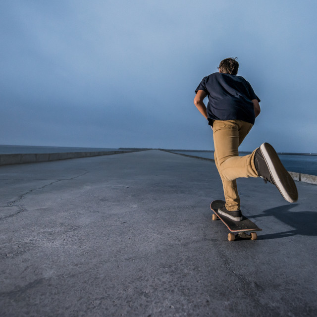 """""""Skateboarder pushing on a concrete pavement"""" stock image"""