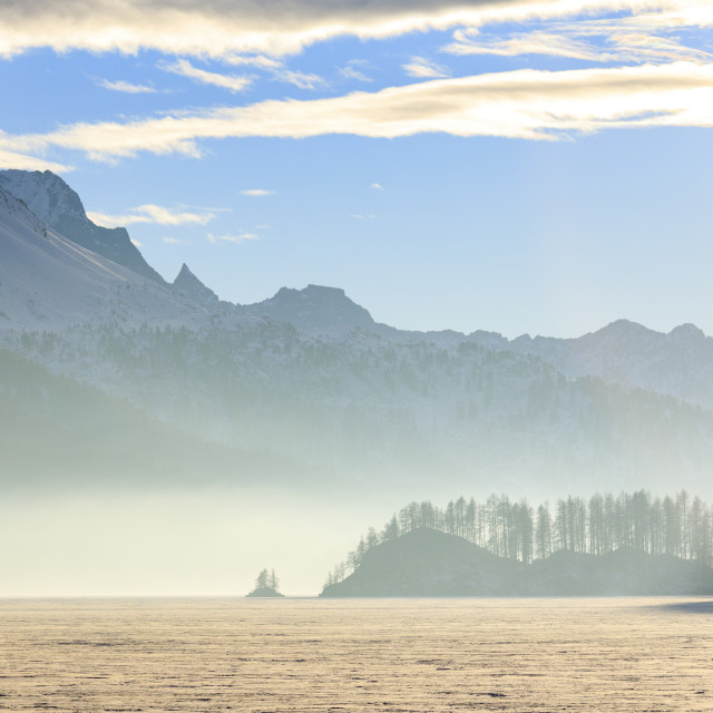 """Mist at sunset on Lake Sils covered with snow Maloja Canton of Graubunden..."" stock image"