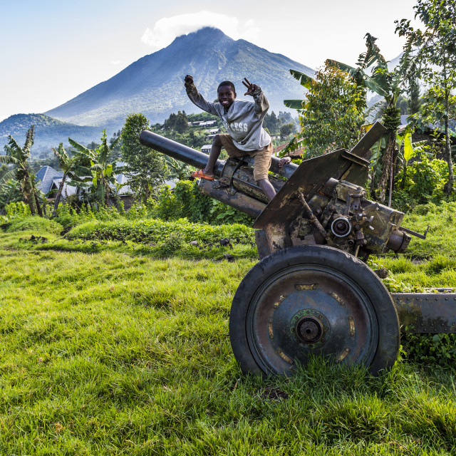 """Boys posing on an abandoned artillery in the Virunga National Park,..."" stock image"