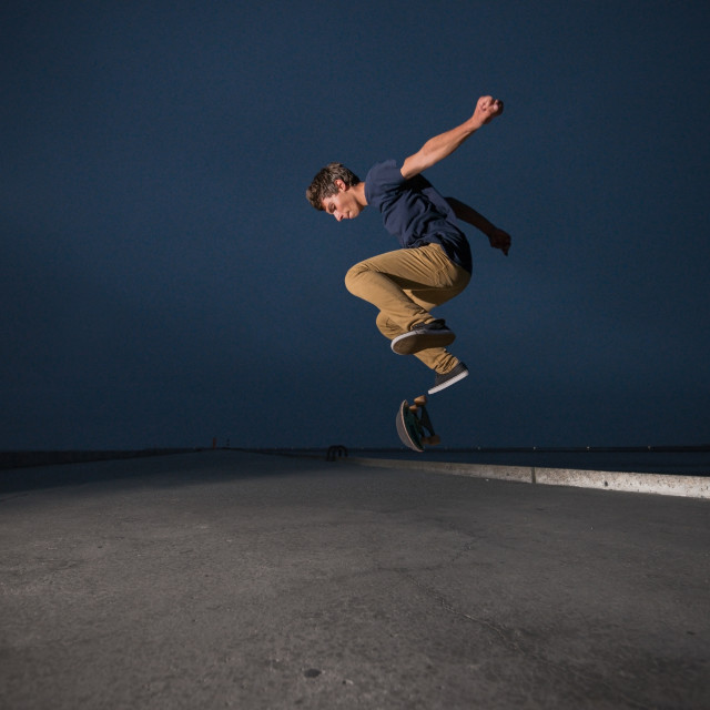 """""""Skateboarder performing a ollie flip on a concrete pavement"""" stock image"""