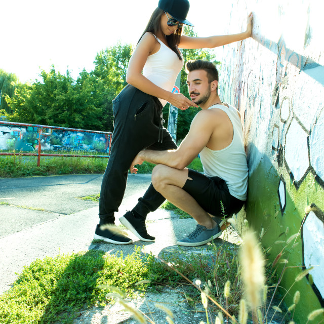 """Young Couple standing at a wall in a urban environment"" stock image"
