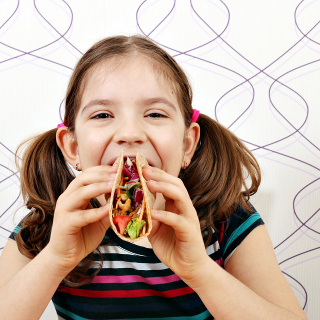 """hungry little girl eating tacos"" stock image"
