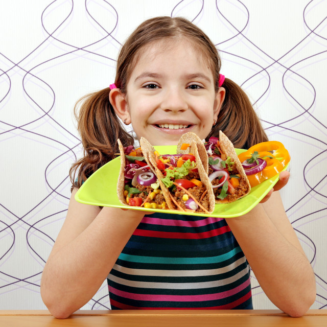 """happy little girl with tacos for lunch"" stock image"