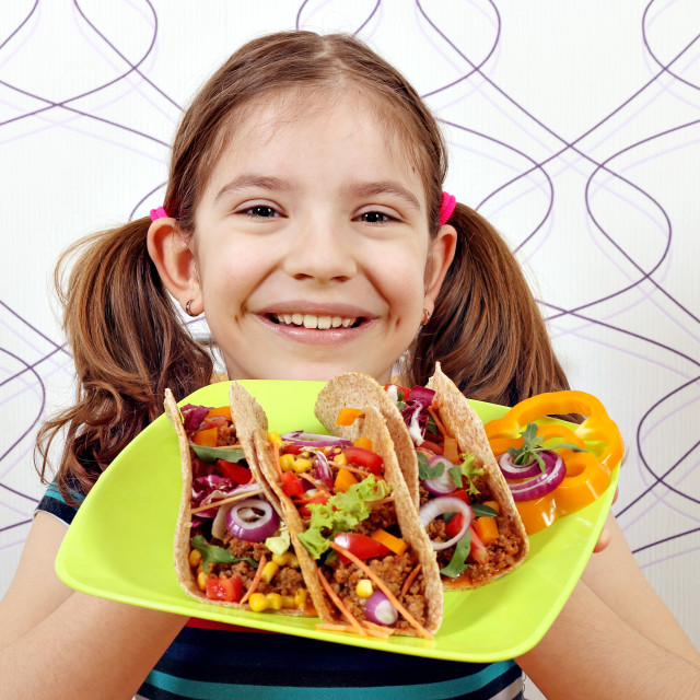 """happy little girl with tacos on plate"" stock image"
