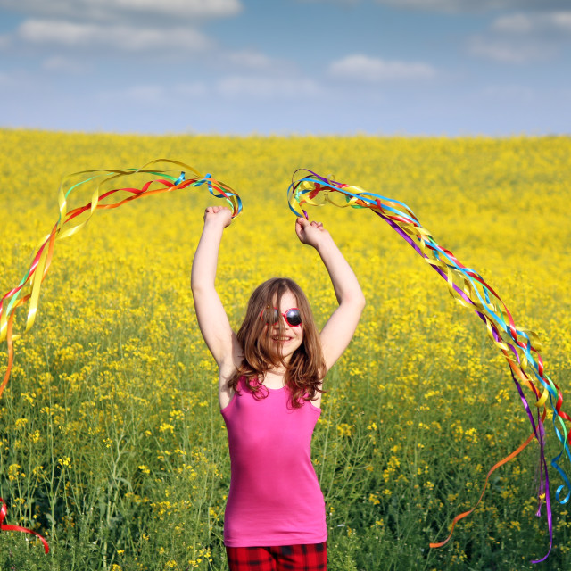 """happy little girl waving with colorful ribbons on field"" stock image"