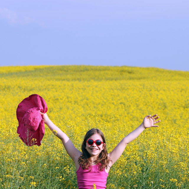 """little girl with hands up on yellow flowers field summer season"" stock image"